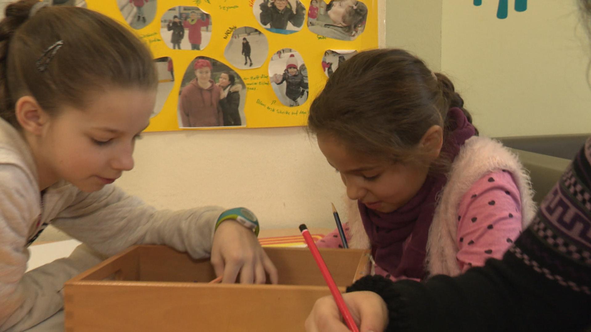 Zwei Mädchen sitzen zusammen an einem Tisch