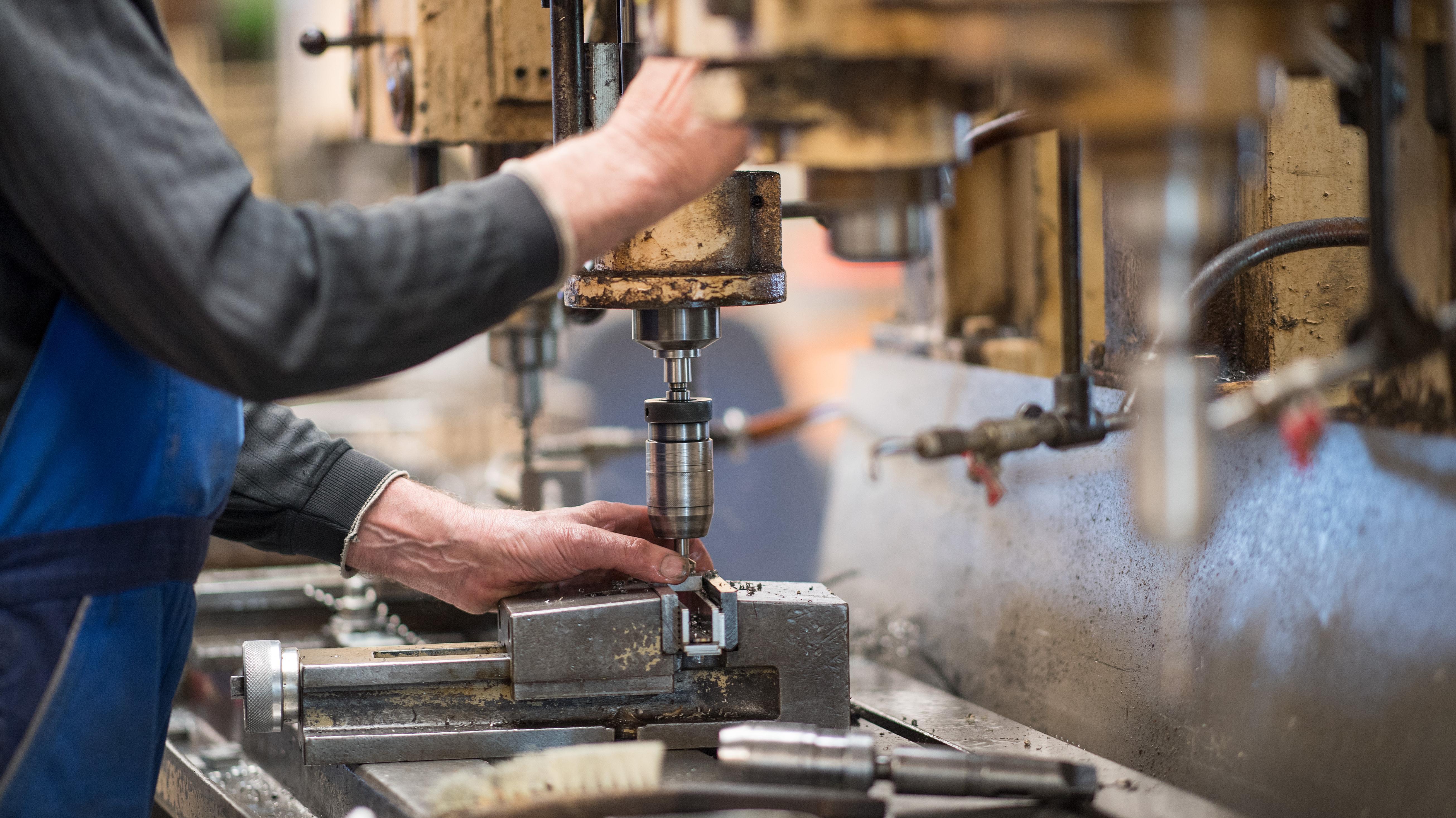 Eine Fachkraft bedient in der Produktionshalle eine Maschine zur Verarbeitung von Metall