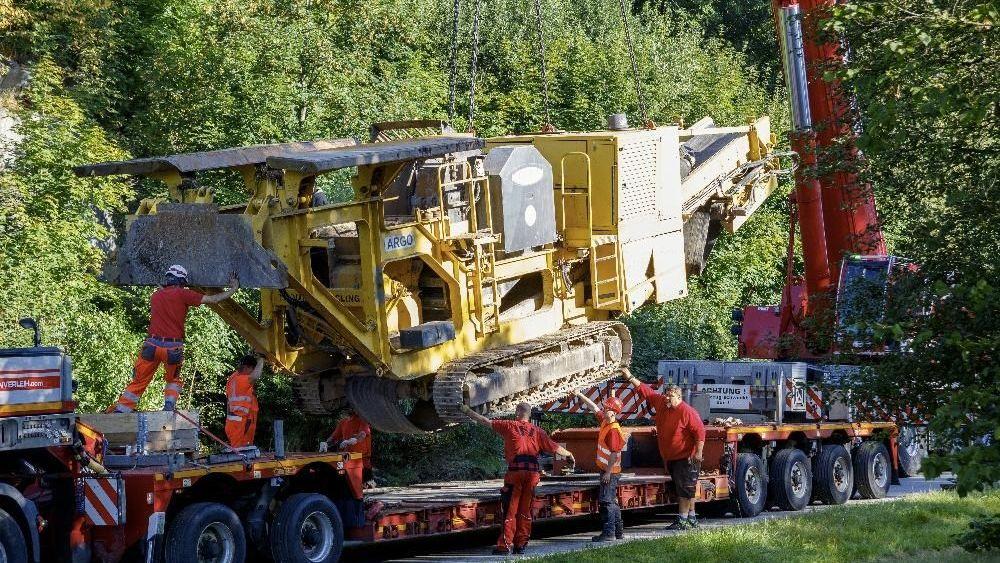 Die gelbe Brechermaschine wird von einem Spezialkran und mehreren Arbeitern auf einen Transporter verladen