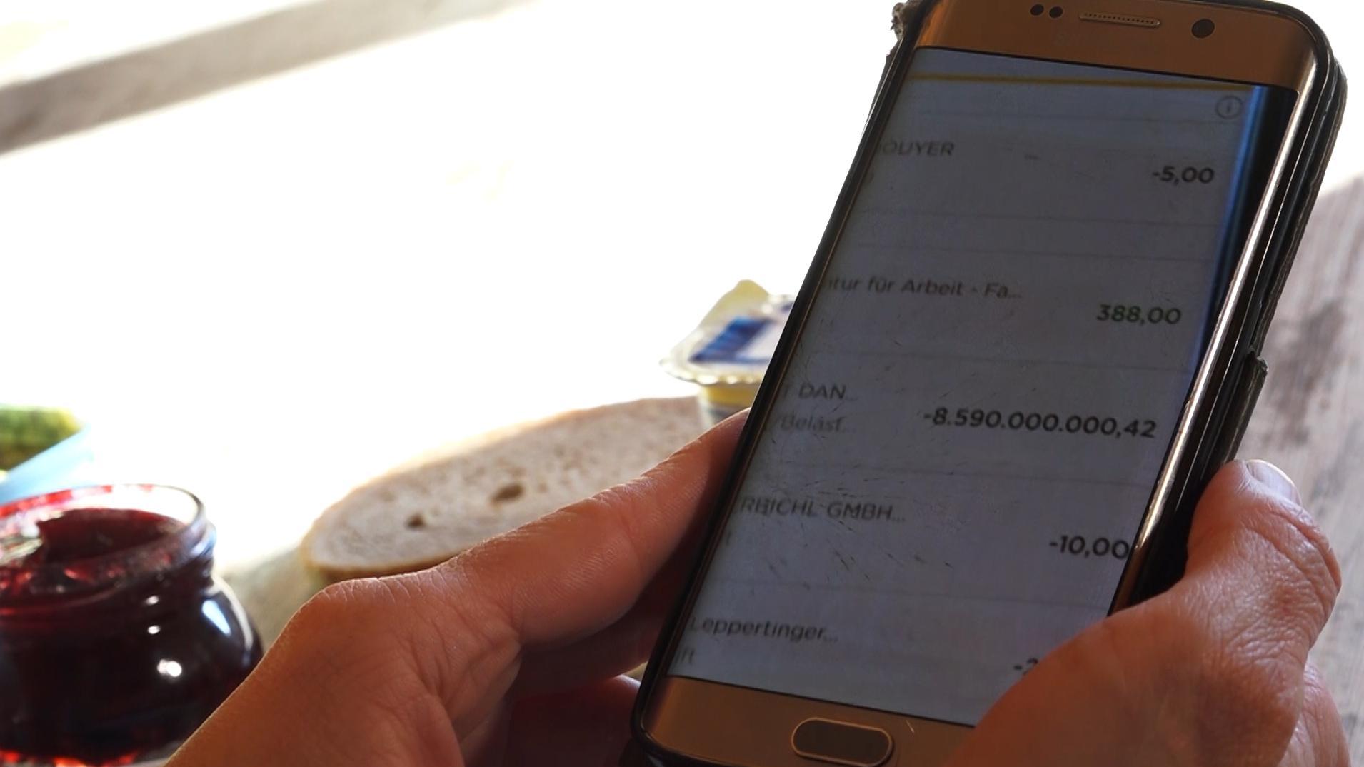Auf dem Handy ist der Kontostand über eine Banking-App zu sehen.