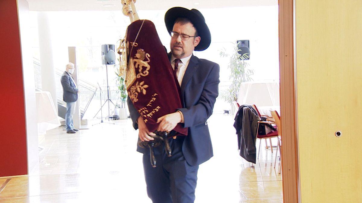 Ein Rabbiner trägt die Thorarolle