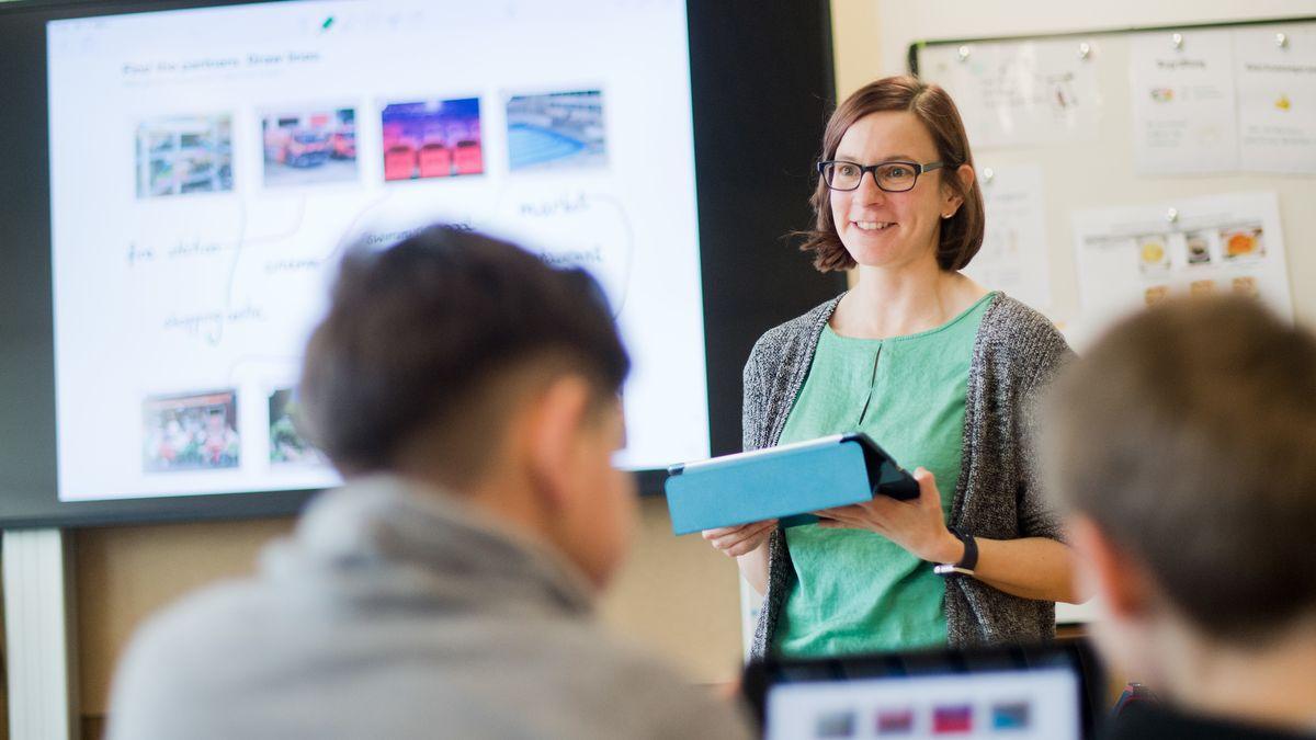 Eine Lehrerin steht mit einem iPad vor einer digitalen Schultafel im Englischunterricht vor der Klasse.