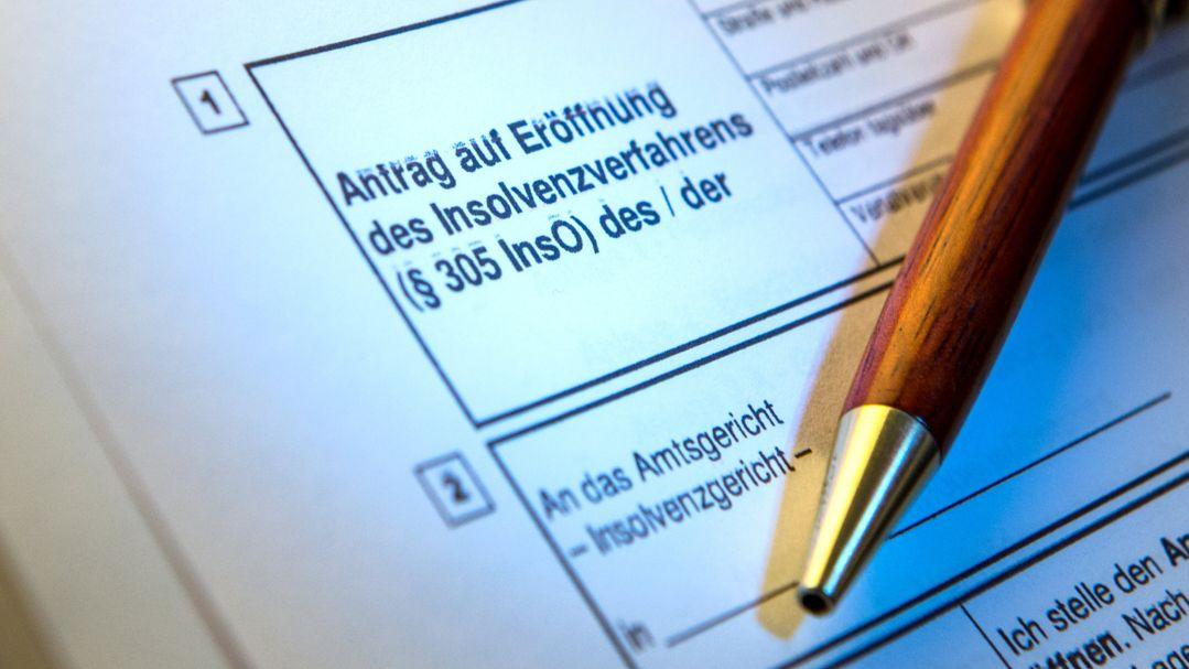 Ein Kugelschreiber liegt auf einem Antrag zur Eröffnung eines Insolvenzverfahrens.