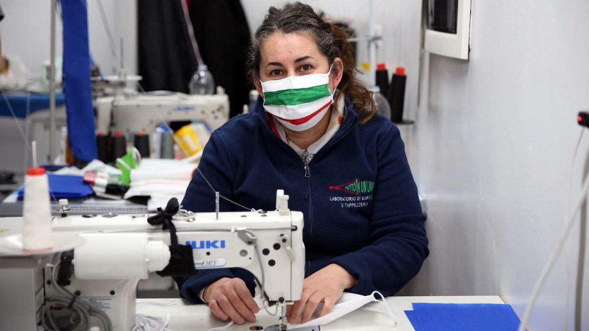 Eine italienische Näherin sitzt an einer Nähmaschine und produziert Schutzmasken. Sie selbst trägt eine Maske in den italienischen Nationalfarben rot, weiß und grün.