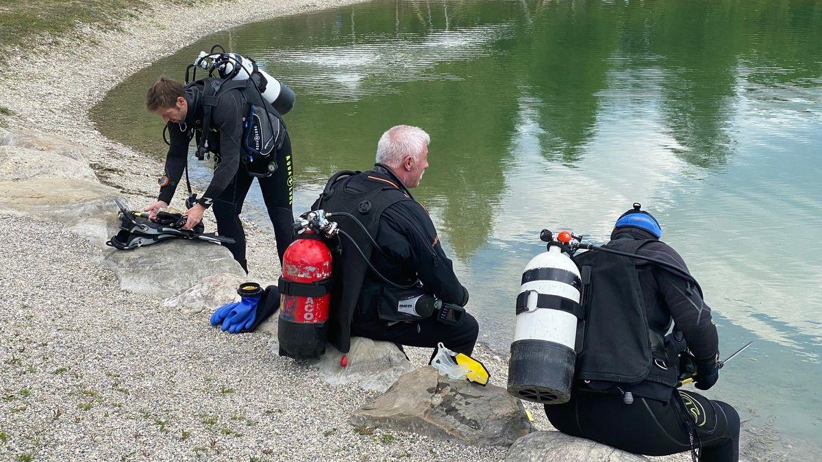 Drei Männer in Tauchausrüstung sitzen am Ufer des Fridolfinger Sees mit Sauerstoffflaschen