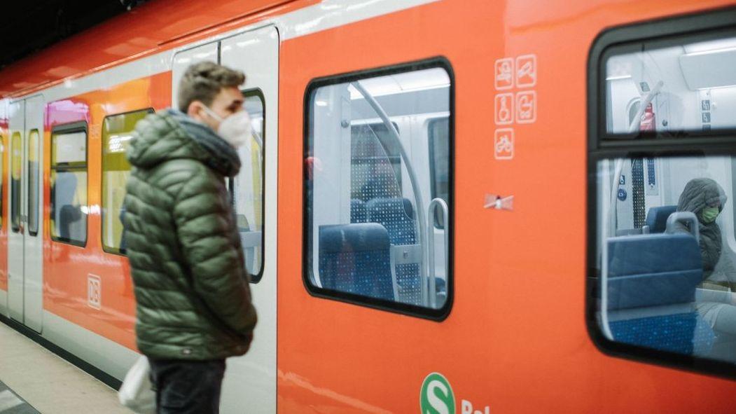 Fahrgast mit FFP2-Maske an einer S-Bahn-Haltestelle