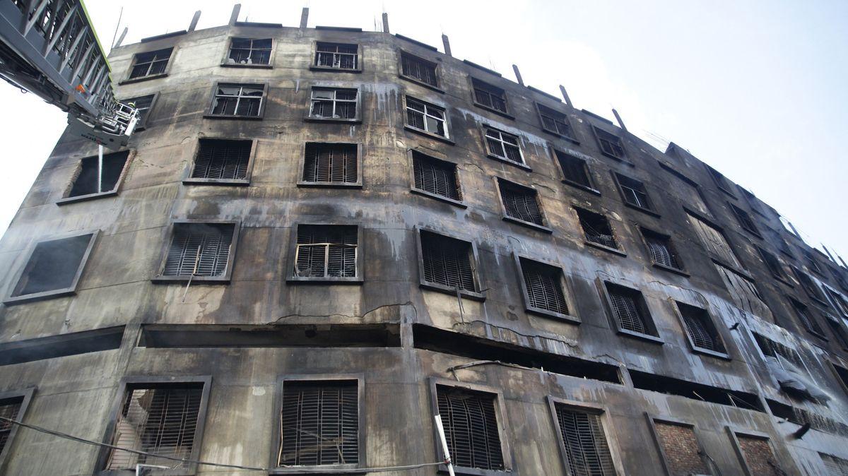 Feuerwehrleute auf einer Drehleiter löschen einen Brand in einem Fabrikgebäude.