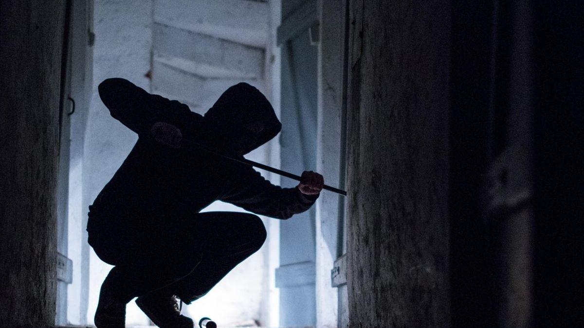 Ein Mann mit Kapuze stemmt mit einem Brecheisen nachts eine Tür auf. (Symbolbild)