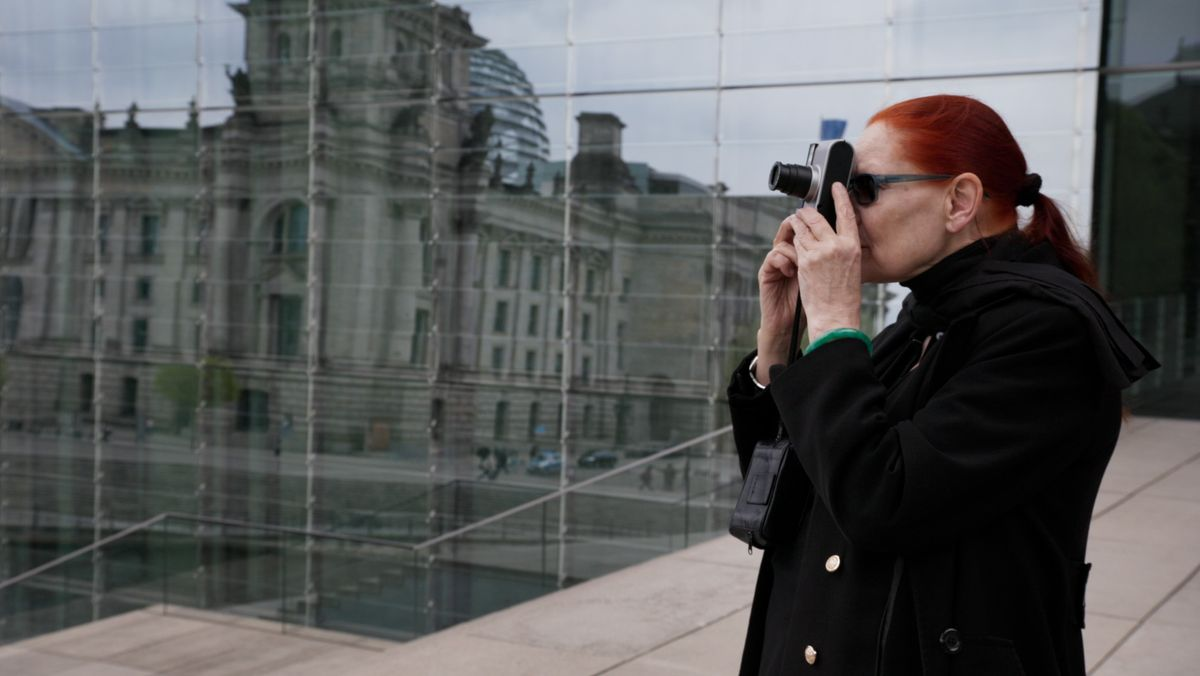 Katharina Sieverding steht vor dem Berliner Reichstag und schaut durch ihre Kleinbildkamera
