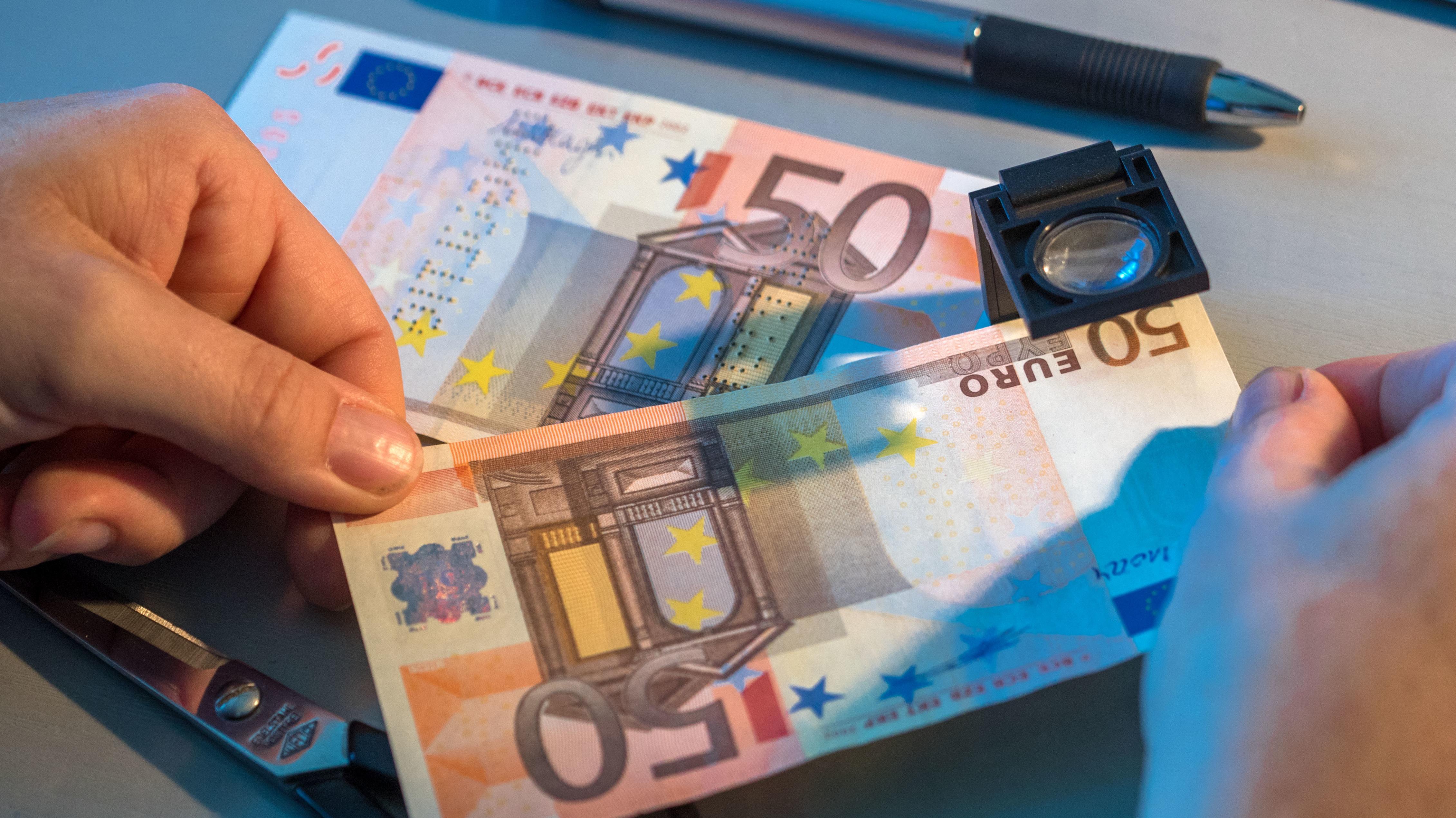 Gefälschte Euro-Geldscheine unter einer Lupe