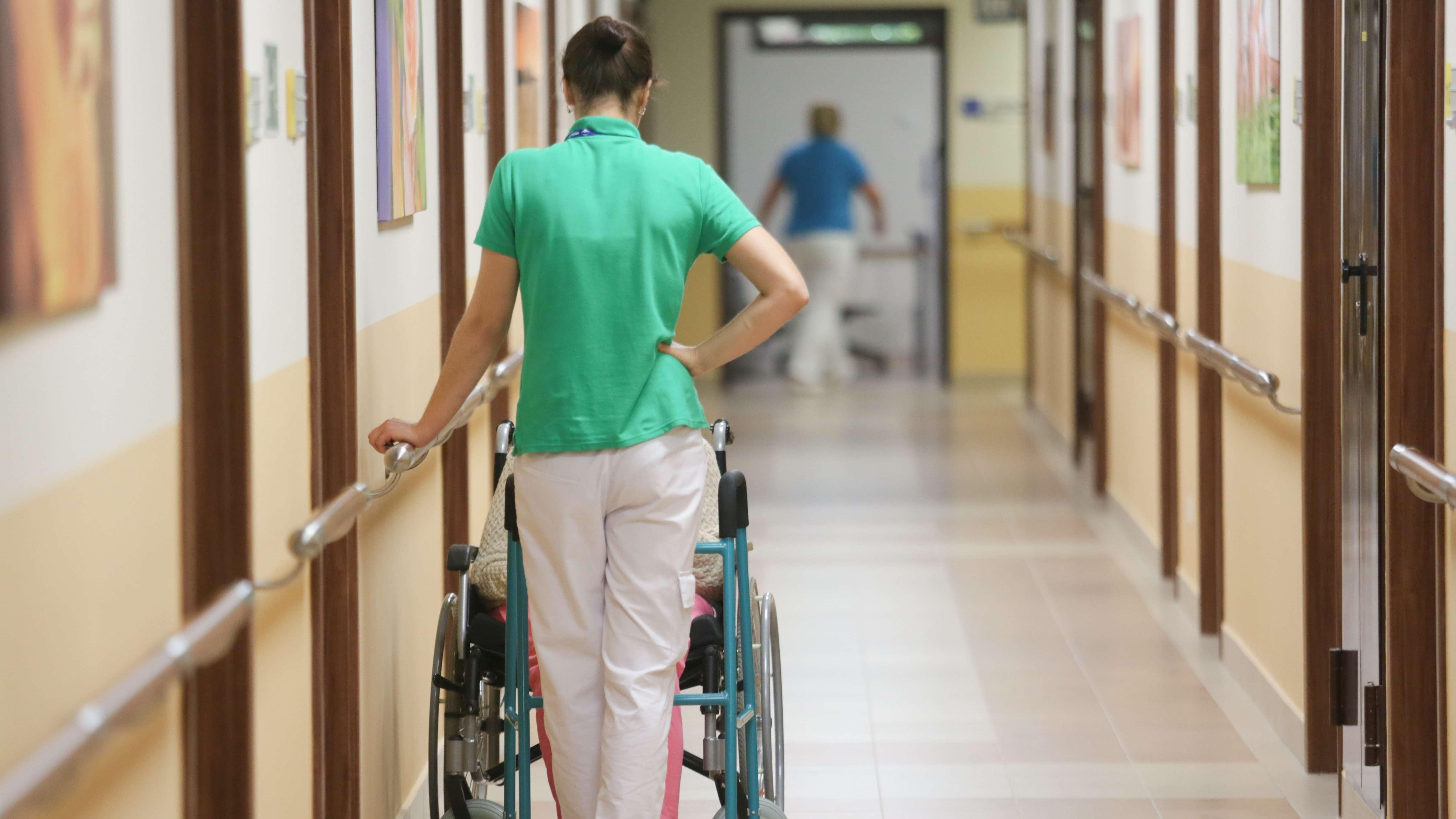 Hohe Verantwortung, hohe Qualifikation, niedriges Gehalt: Eine Altenpflegerin mit einer Dame im Rollstuhl.