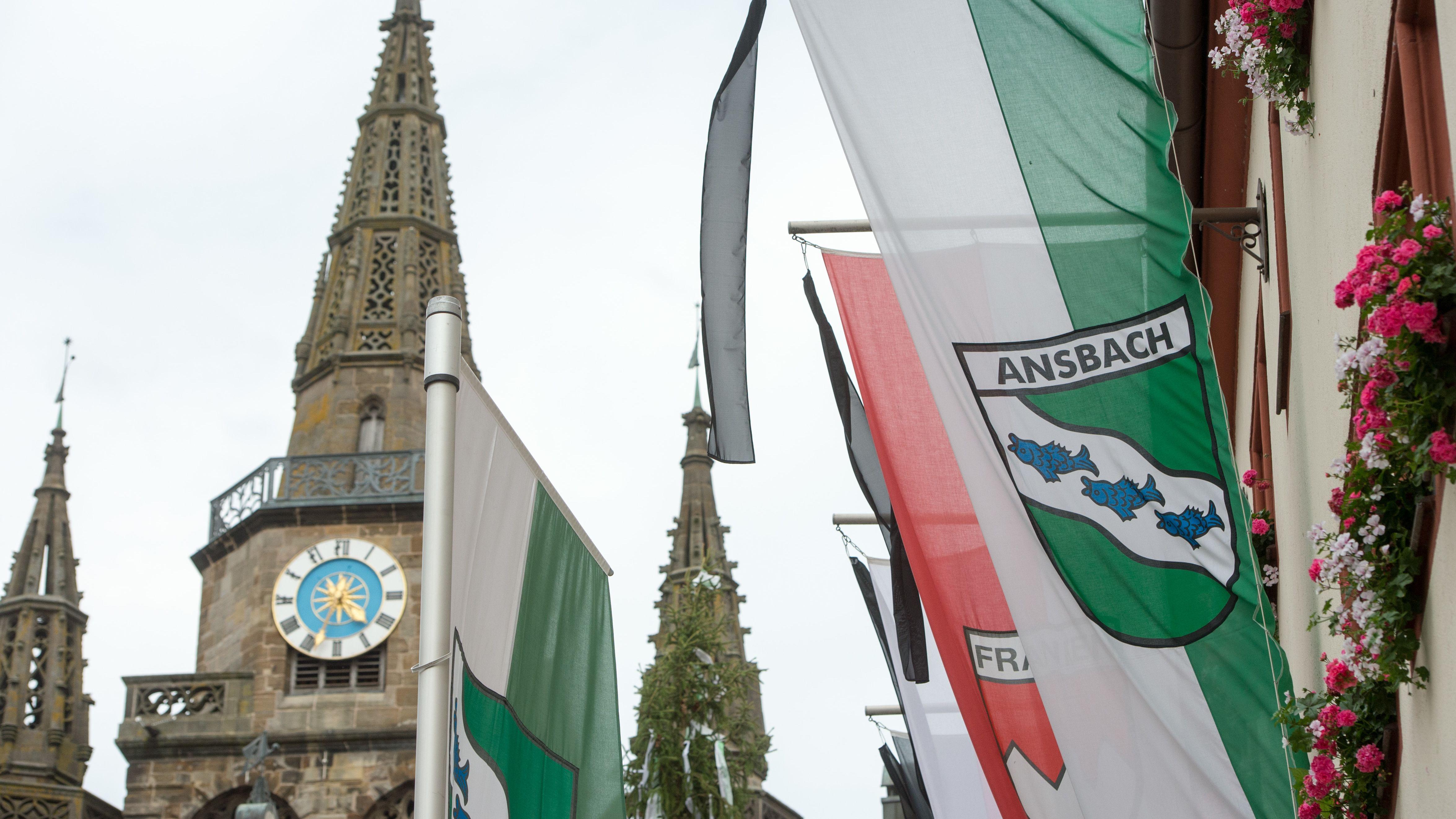 """Grün-weiße Fahne mit Aufschrift """"Ansbach"""" neben Kirchturm"""