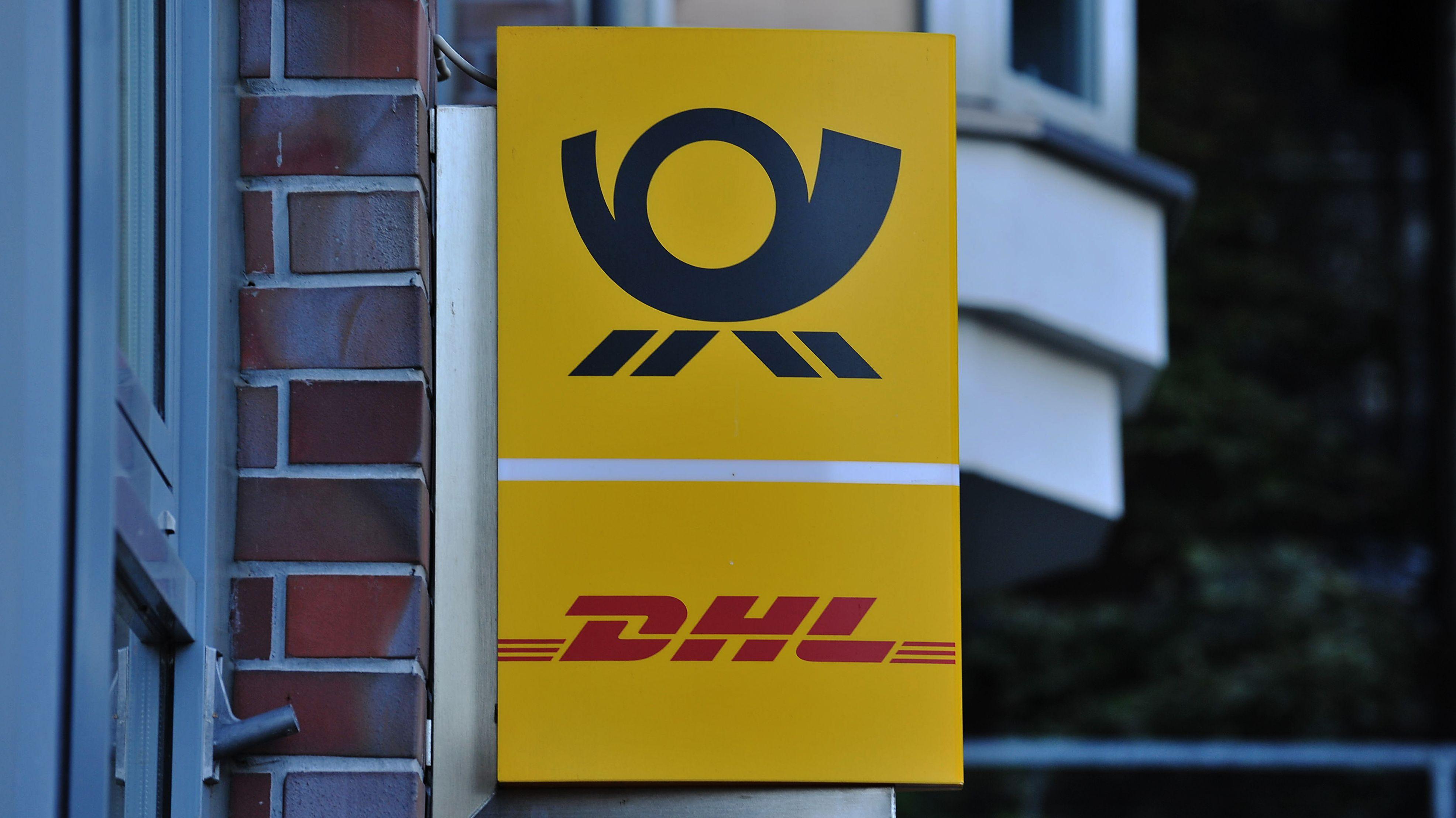 Firmenschild der Post hängt an der Fassade eines Hauses.