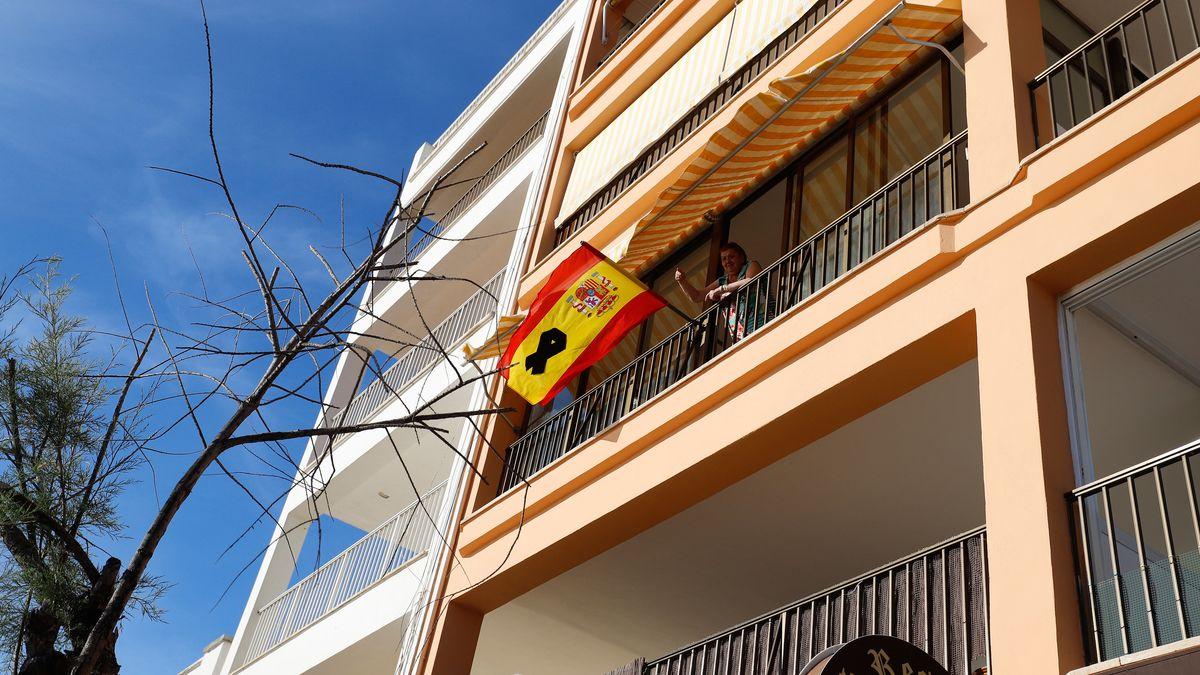 Eine Frau winkt von ihrem Balkon neben der spanischen Flagge mit einer schwarzen Schleife zum Gedenken an die COVID-19 Toten.