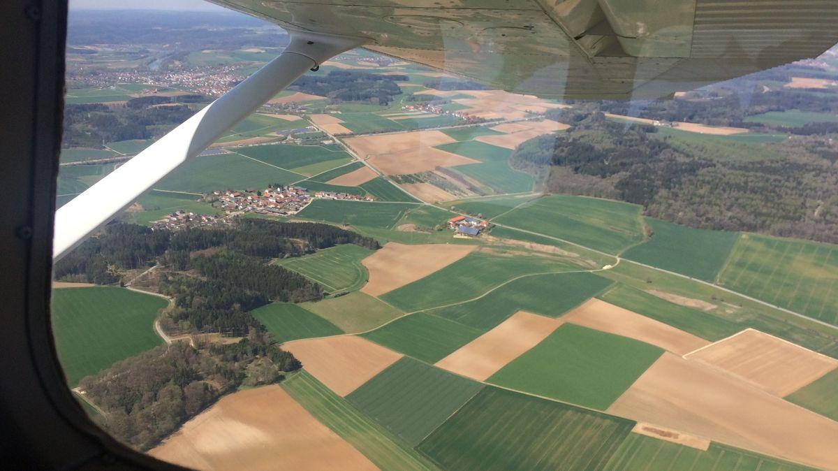 Der Blick auf Felder und Wälder aus dem Flugzeug