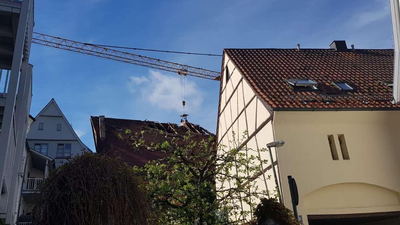 Arbeiter in einem Korb an einem Kran arbeiten am Dachstuhl des Memminger Färberhauses