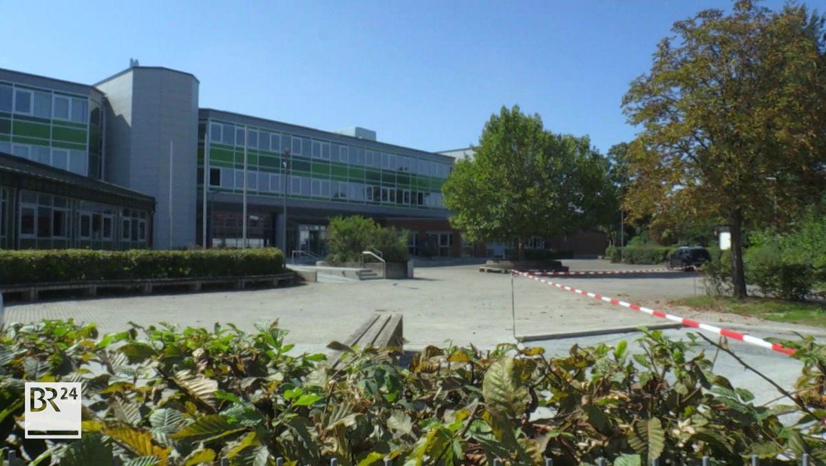 Vor einer Schule ist ein weiß-rotes Absperrband über den Pausenhof gezogen.