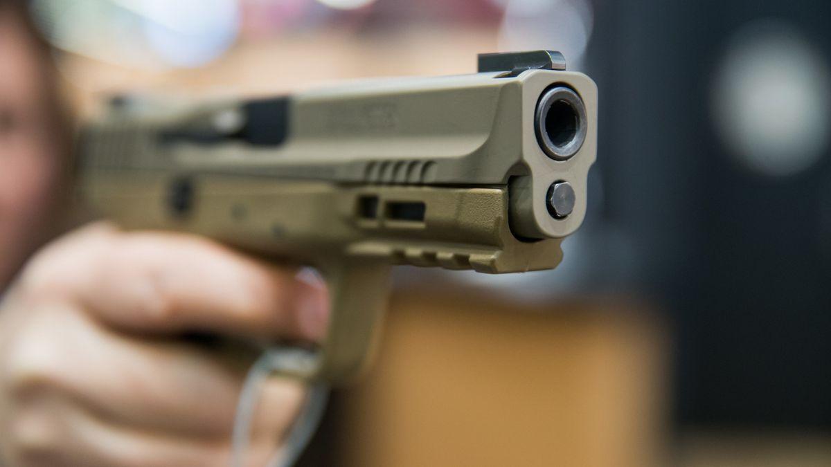 Eine Frau hält auf einer Fachmesse eine 9 Millimeter Handfeuerwaffe in der Hand (Archivbild).