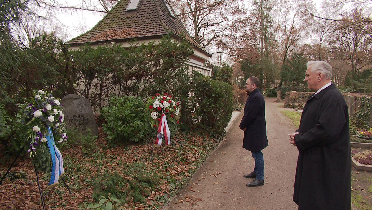 Joachim Herrmann (CSU) und Florian Janik (SPD) stehen am Friedhof vor Kränzen.