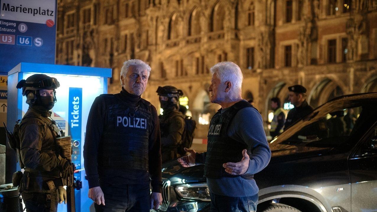 """Szene aus """"Unklare Lage"""": Udo Wachtveitl und Miroslav Nemec stehen mit Komparsen in SEK-Uniform diskutierend am Marienplatz in München"""