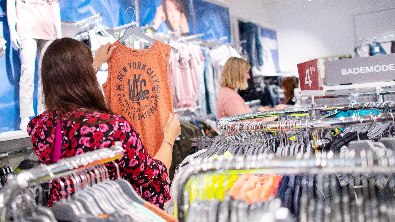 Mitarbeiter sortieren in einem Textilgeschäft Kleidungsstücke