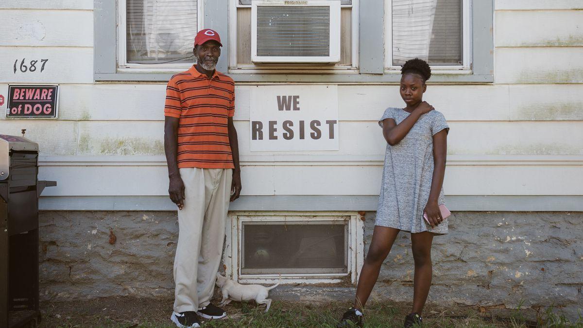"""Zwei Menschen stehen vor einer Hauswand, zwischen ihnen auf der Wand ein Schild: """"We resist"""" steht darauf."""