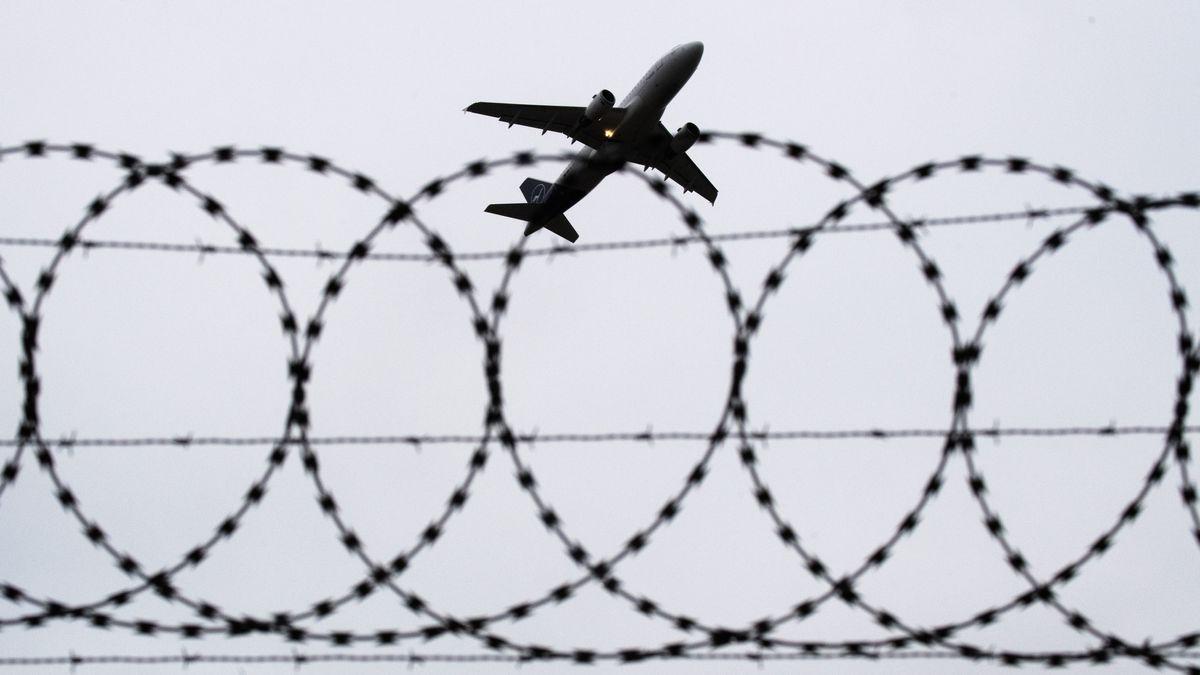 Abschiebung am Flughafen Hannover (Symbolbild): Ein Flugzeug von Lufthansa startet - fotografiert durch Stacheldraht am Flughafenzaun.