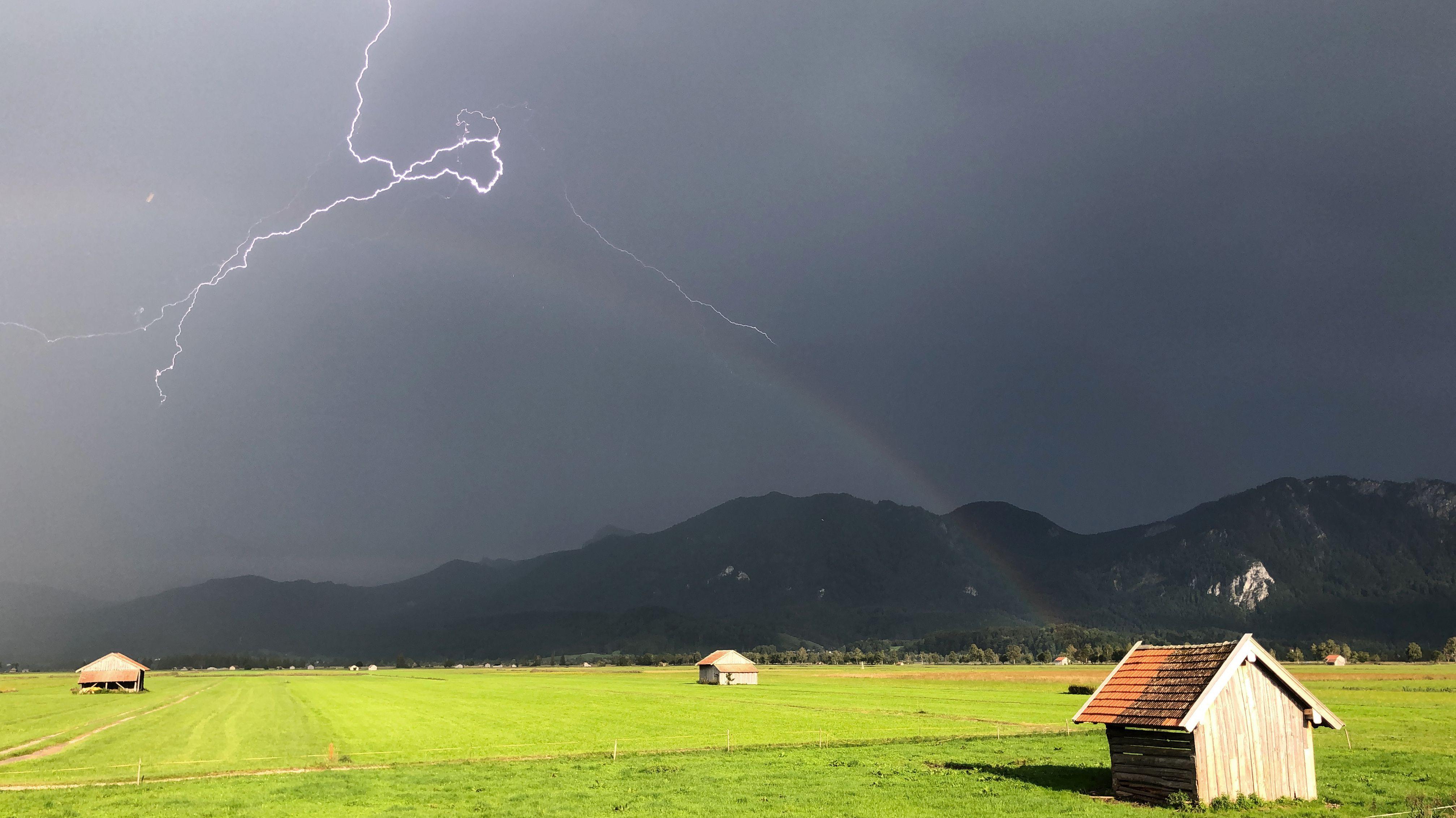 24.08.2019, Schlehdorf: Ein Blitz zuckt über den bayerischen Voralpen, während über einer Weide ein Regenbogen erkennbar ist.