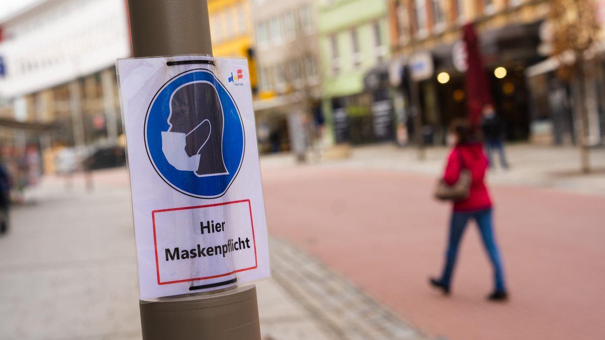 """Eine Frau geht an einem Plakat mit der Aufschrift """"Hier Maskenpflicht"""" vorbei. Die Stadt Hof hat weiter die höchsten Corona-Infektionszahlen."""