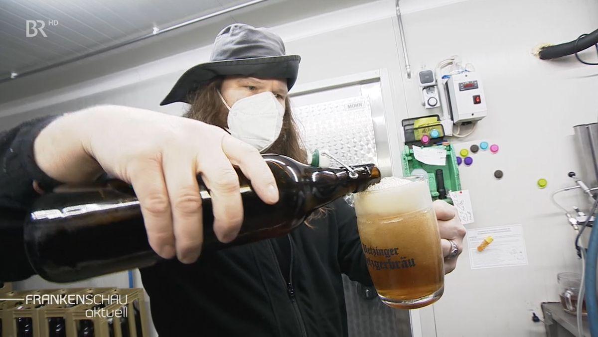 Ein Mann schenkt in einer Braurei aus einer Flasche Bier in ein Glas.