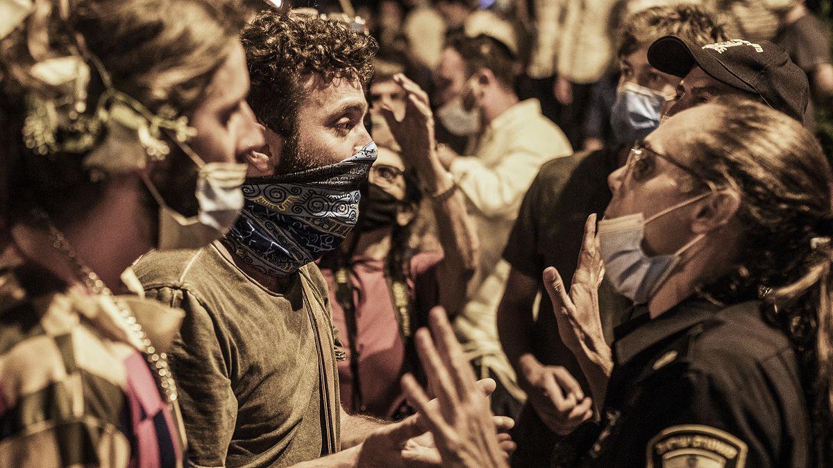 Eine Polizistin mit Mundschutz spricht mit Demonstranten, als am 21. Juli 2020 tausende  gegen den israelischen Ministerpräsidenten in der Nähe seiner offiziellen Residenz protestierten.