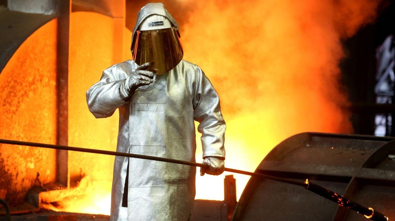 Nordrhein-Westfalen, Duisburg: Ein Stahlarbeiter prüft am Hochofen 8 bei ThyssenKrupp die Stahlqualität nach dem Abstich.
