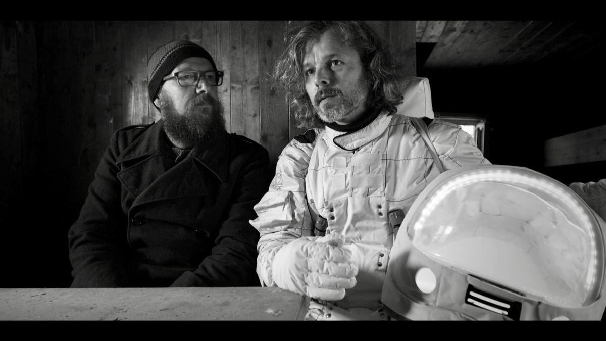 Die Musiker Sebastian Horn und Gerd Baumann sitzen an einem Tisch und schauen nachdenklich. Baumann trägt einen Astronautenanzug, sein Weltraumhelm liegt neben ihm.