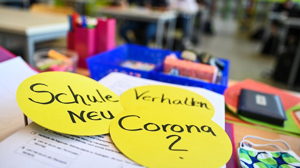 """Schüler sitzen im Klassenzimmer, im Vordergrund liegen auf dem Lehrerpult drei kreisrunde Papierschilder mit den Worten """"Schule neu"""", """"Verhalten"""" und """"Corona"""""""
