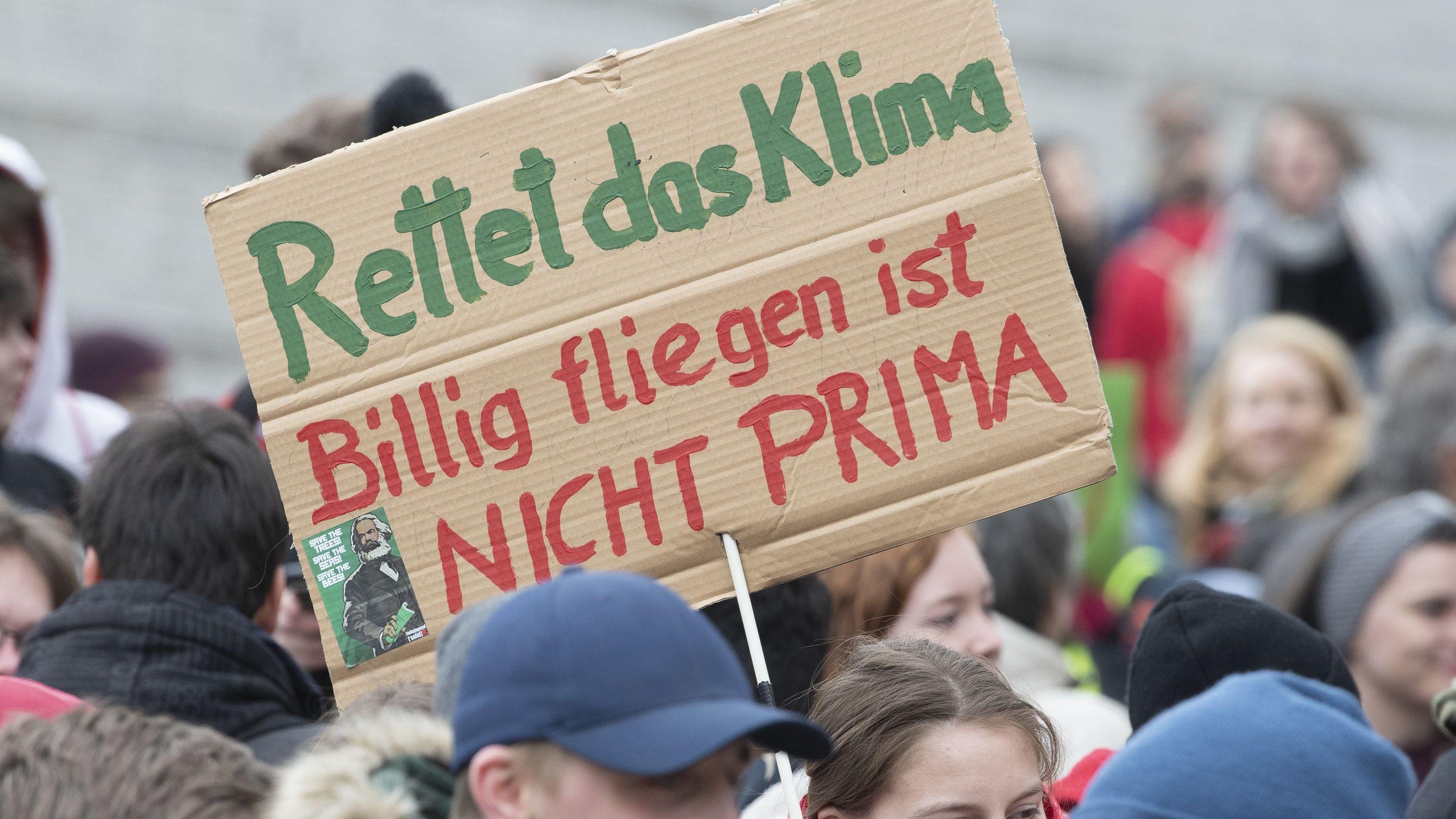 """Symbolbild Klimastreik: Demonstranten halten Plakate mit der Aufschrift """"Rettet das Klima, Billig fliegen ist nicht prima""""."""