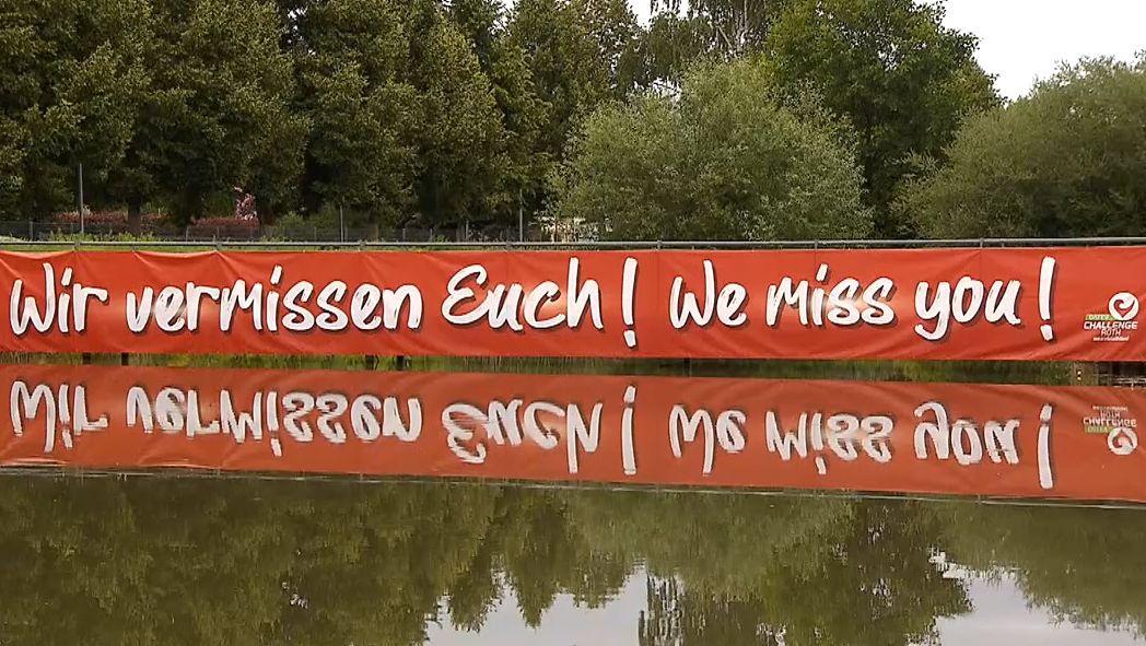 """Rotes Banner mit der Aufschrift """"Wir vermissen Euch!"""" spiegelt sich in einem See."""