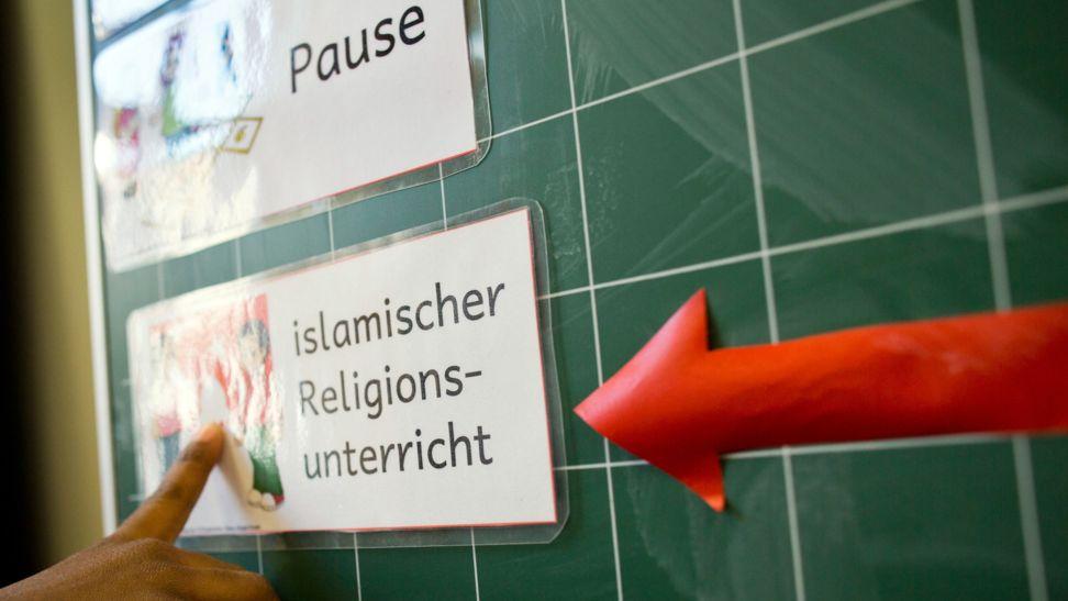 ARCHIV - 11.02.2014, Hessen, Frankfurt/Main: Auf einer Tafel wird durch einen roten Pfeil angezeigt, dass in der nächsten Stunde bekenntnisorientierter islamischer Religionsunterricht gehalten wird. An rund 350 Schulen in Bayern wird es vom kommenden Schuljahr an ein Wahlpflichtfach «Islamischer Unterricht» geben.