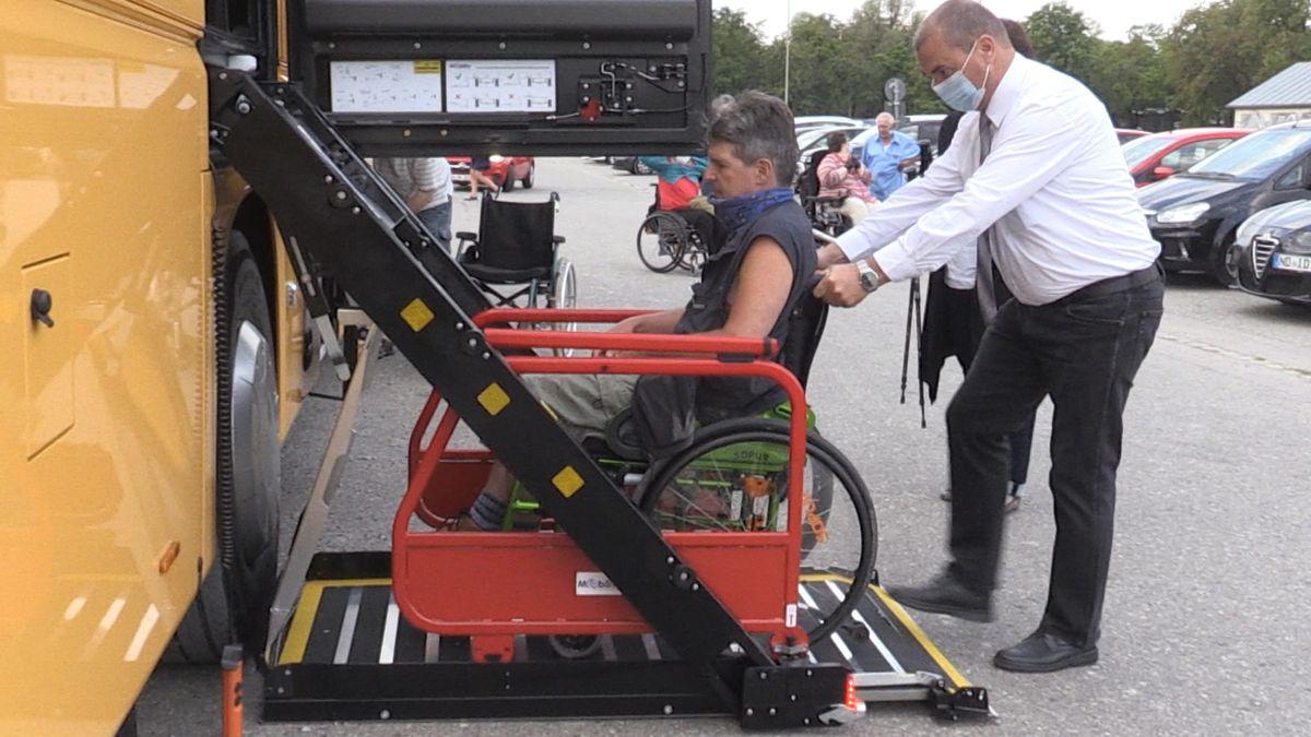 Männlicher Rollstuhlfahrer auf einer kleinen Hebebühne, die an einem Reisebus angebracht ist.