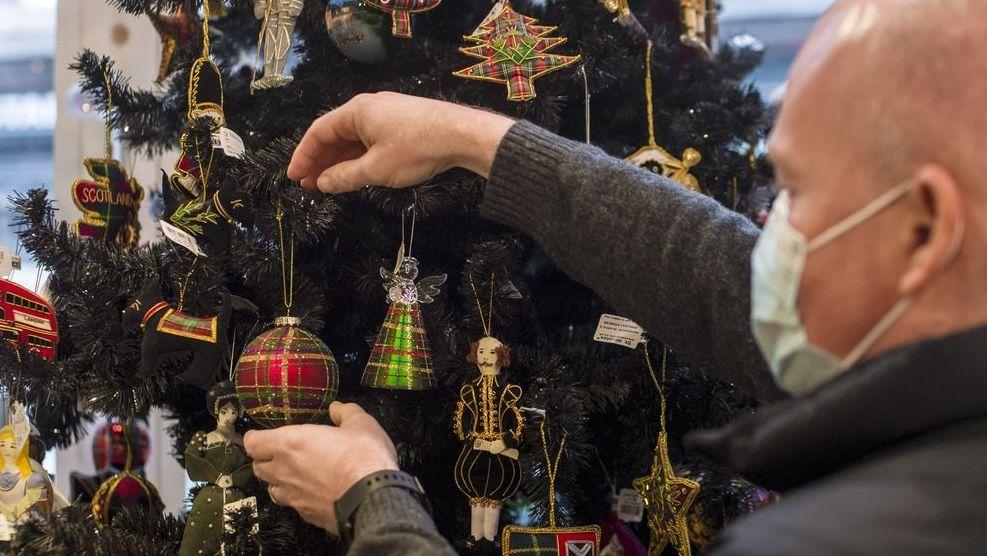 Ein Mann mit Mundschutz hängt eine Christbaumkugel an einen Weihnachtsbaum.