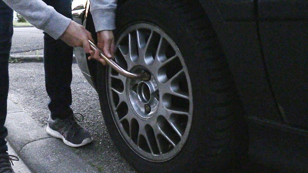 Jemand dreht an den Radmuttern eines Autos (Symbolbild)