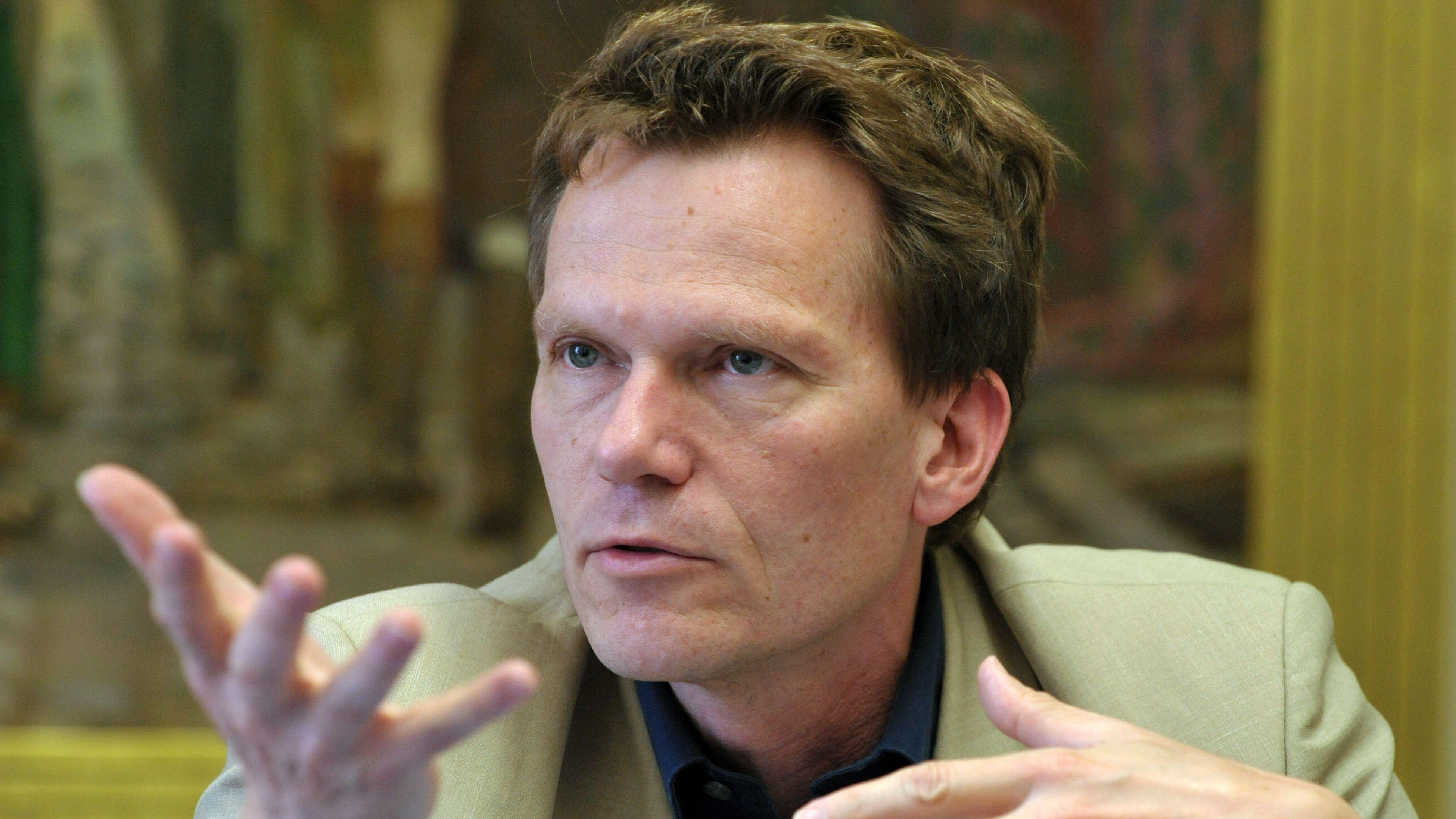 Professor Hartmut Rosa sitzt bei einer Pressekonferenz in Jena gestikulierend vor einem Gemälde.