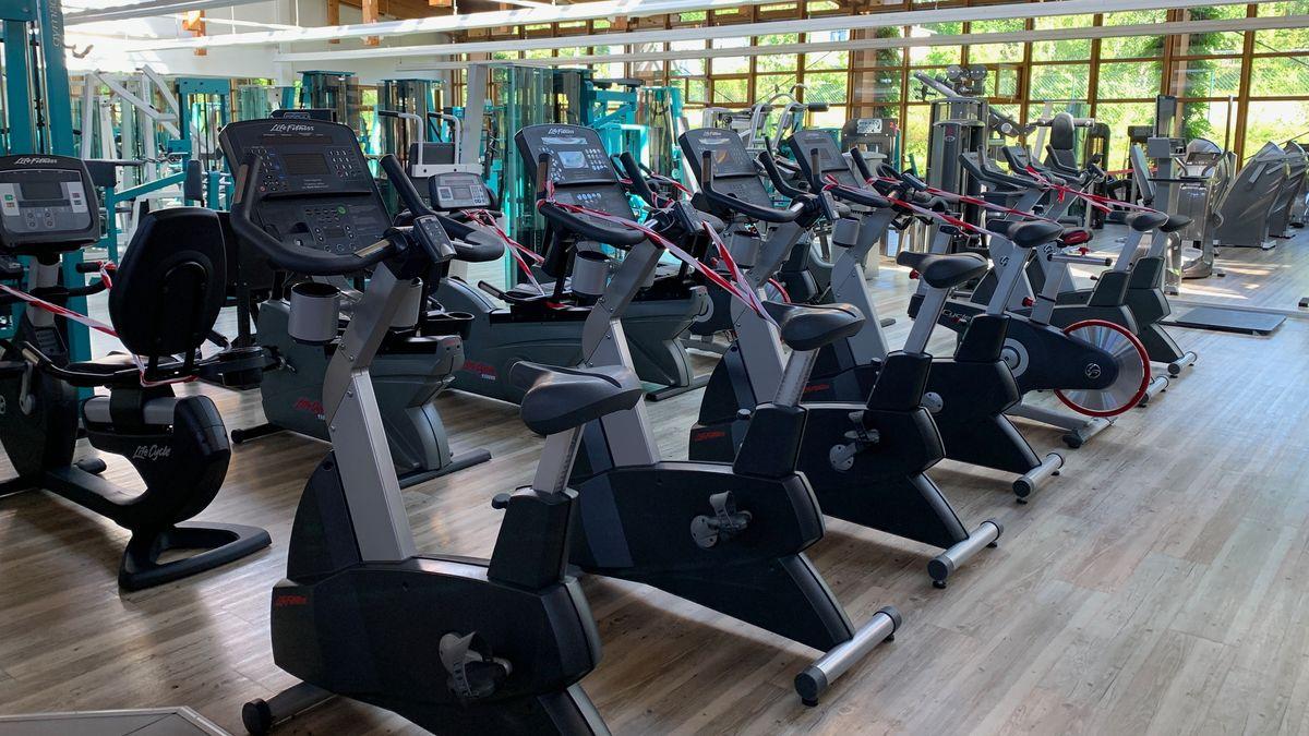 Sportgeräte im Fitnessstudio, von denen einige mit einem Absperrband umwickelt sind.