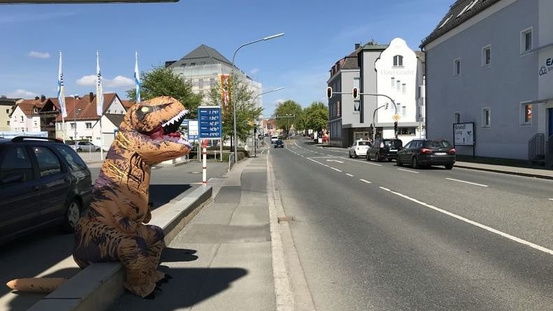 Der Unbekannte im T-Rex-Kostüm sitzt am Straßenrand und ruht sich aus