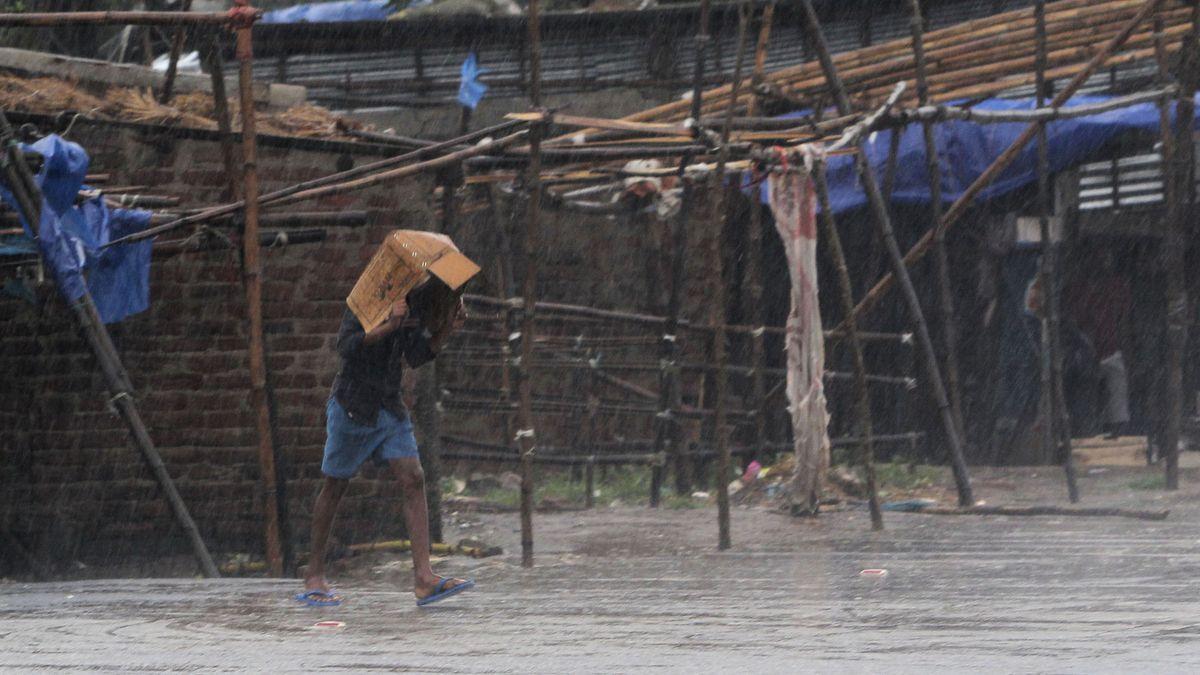 Ein Mann bedeckt seinen Kopf mit einer Kiste und geht durch den Regen im ostindischen Bundesstaat Orissa.