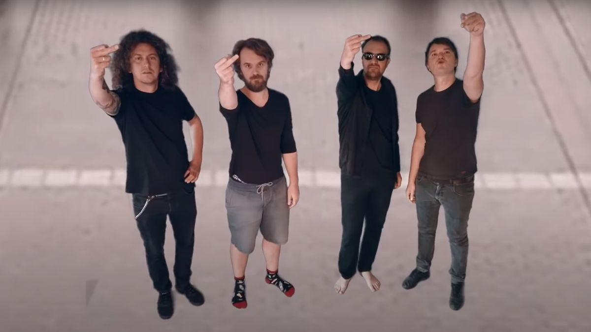 Dier vier Bandmitglieder von Madsen stehen auf einer Straße und zeigen den Stinkefinger