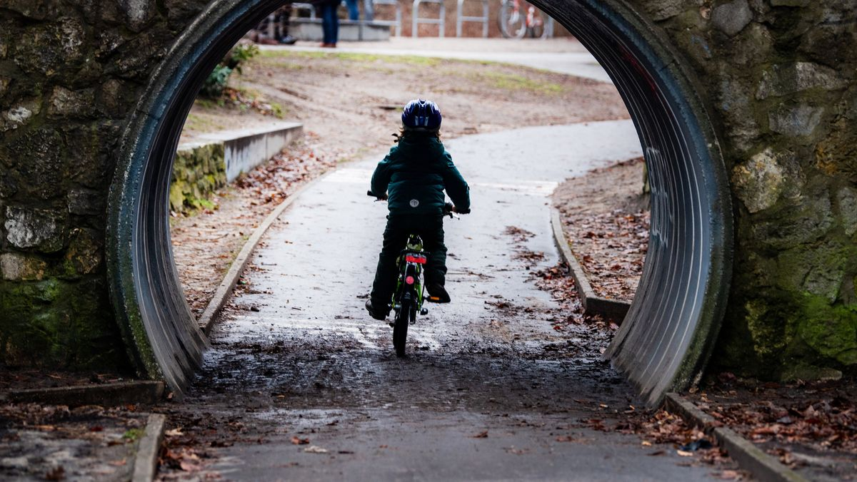 Ein Kind fährt mit dem Fahrrad durch einen Tunnel. (Symbolbild)