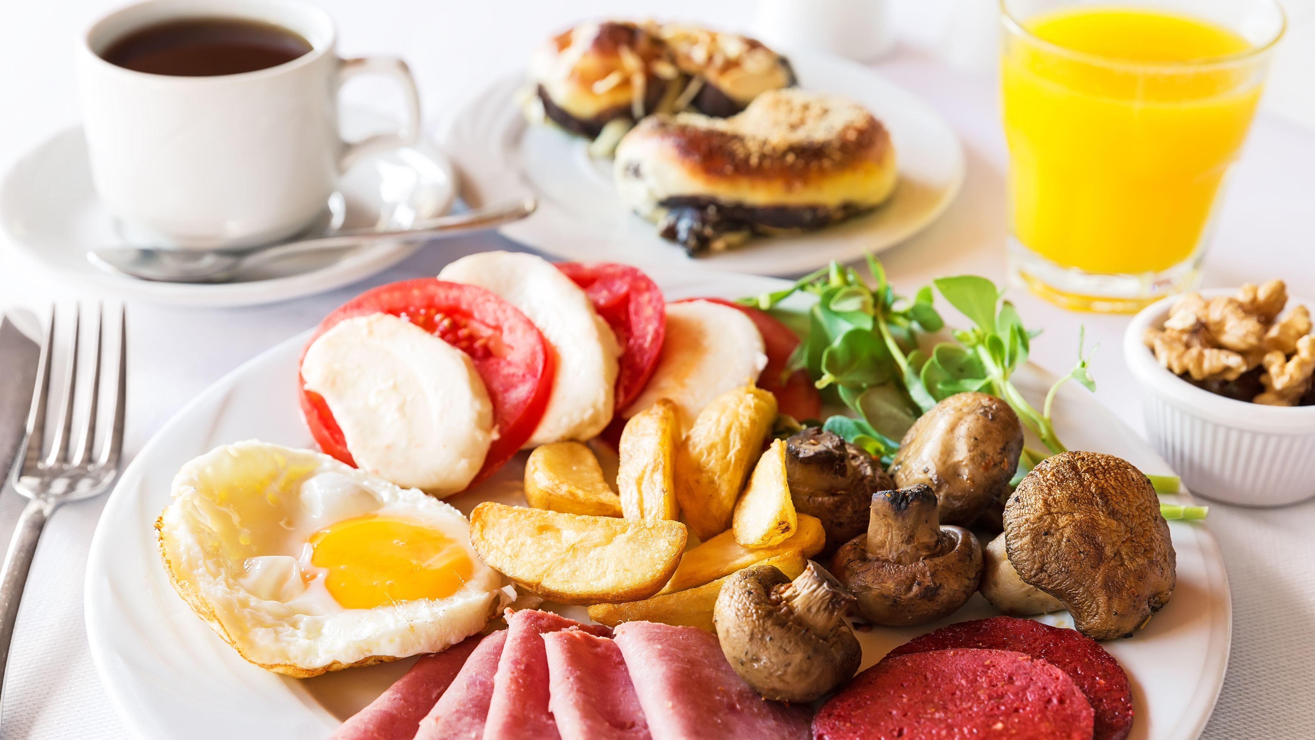Ein reichhaltig gedeckter Tisch mit Kaffee, Croissants, Orangensaft und ein einen Teller mit Wurstaufschnitt, Pilzen, Tomaten-Mozarella-Salat, Champignons und Spiegeleiern.