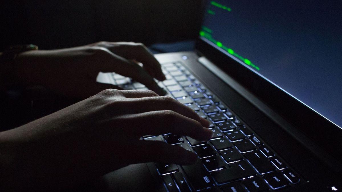 Symbolbild Cybercrime: Hände tippen auf einem Laptop mit Programmcode auf dem Display