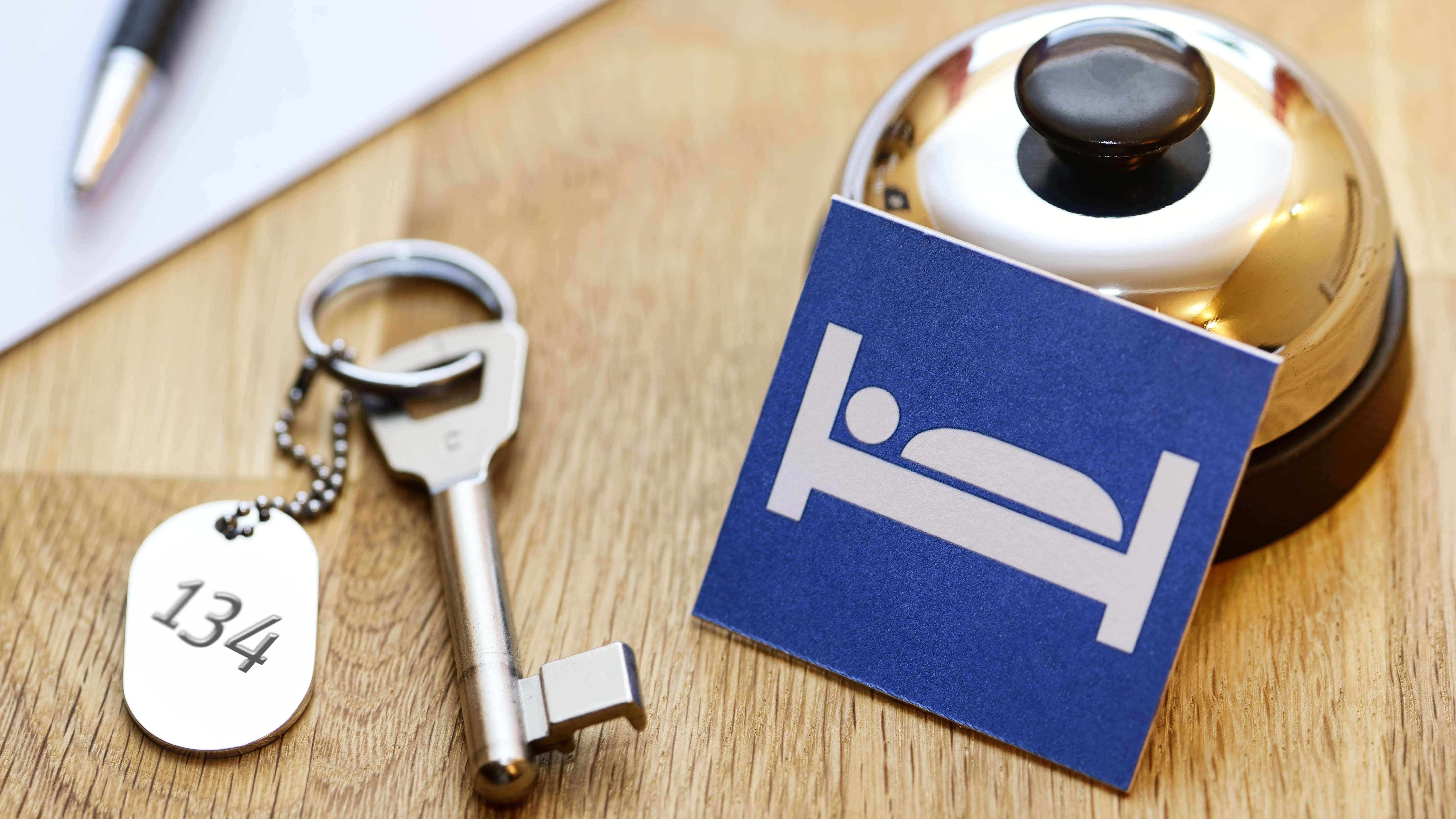 Hotelrezeption mit Zimmerschlüssel und Klingel (Symbolbild)