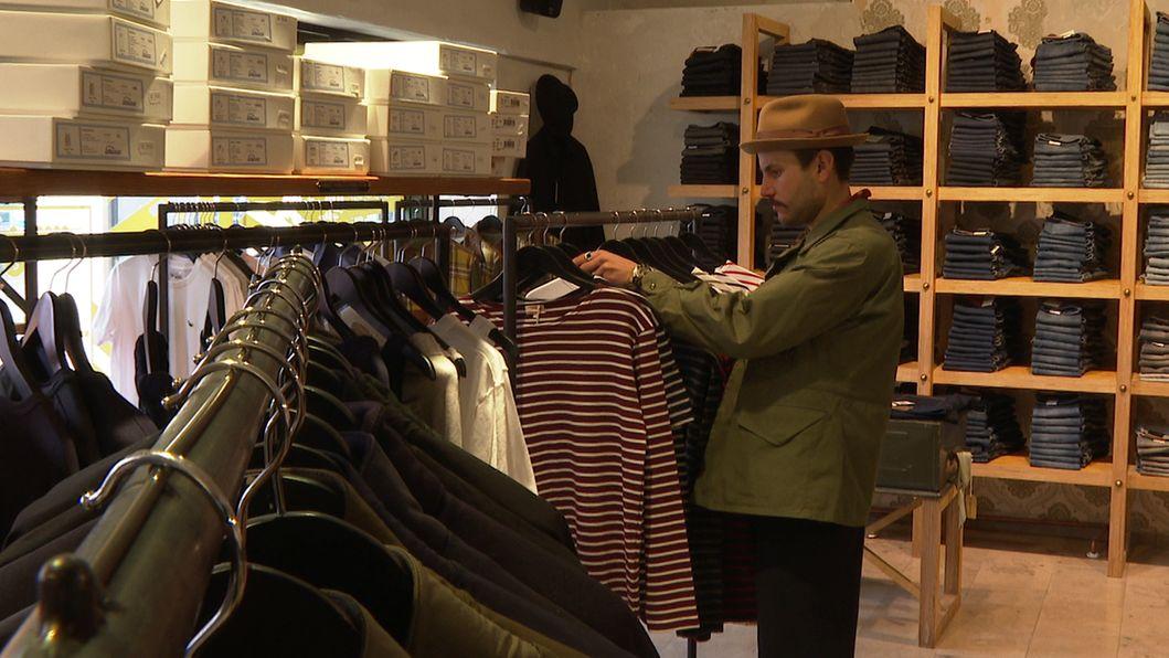 Ein Mann hängt T-Shirts auf Kleiderbügel an einen Kleiderständer